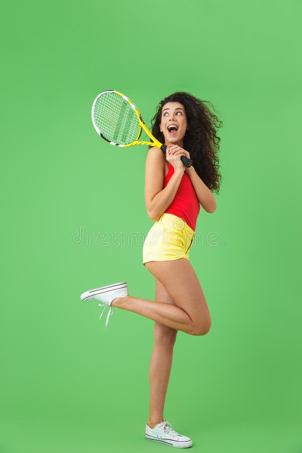 微笑和拿着球拍的白种人女性网球员20s的图象 免版税图库摄影