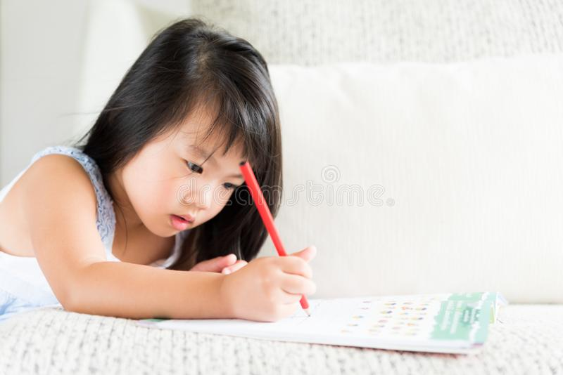 微笑和拿着红色铅笔的愉快的逗人喜爱的小女孩 免版税库存图片