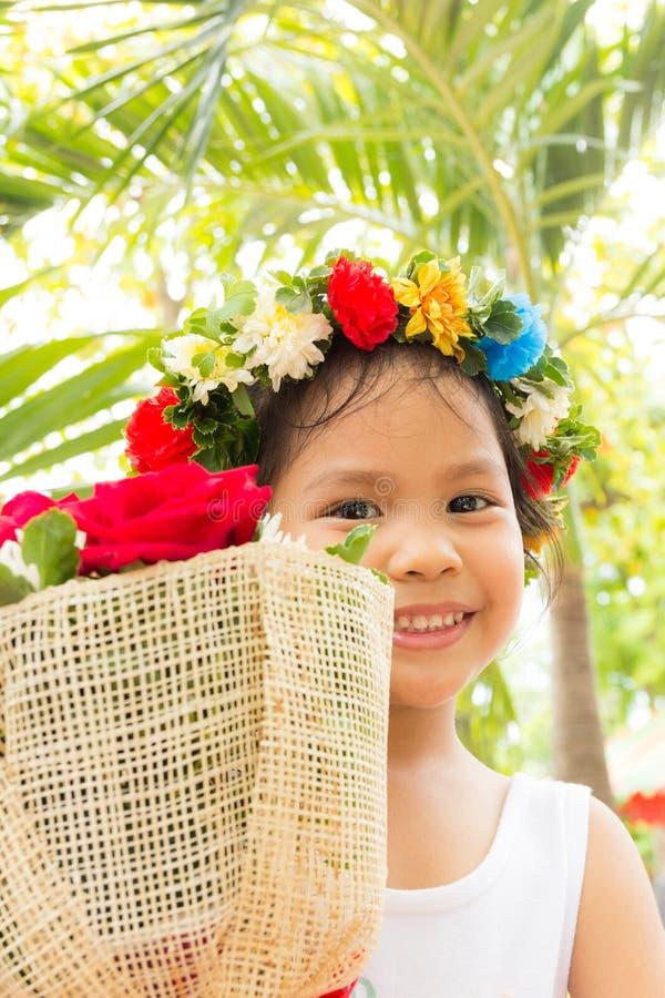 微笑和拿着花束的小女孩起来了 免版税库存照片
