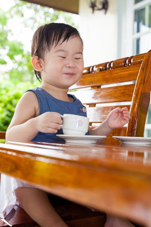 微笑和拿着茶杯的小亚裔女孩 免版税库存图片