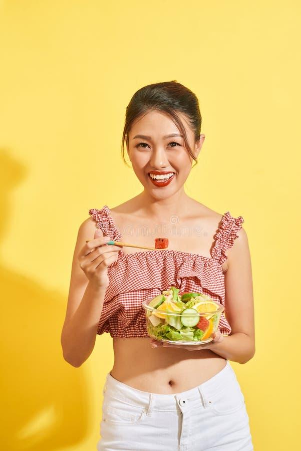 微笑和拿着菜和沙拉在黄色背景的年轻亚裔妇女 免版税库存图片