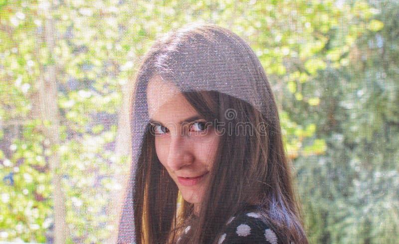 微笑和挥动与照相机的一个俏丽的女孩的画象 库存照片