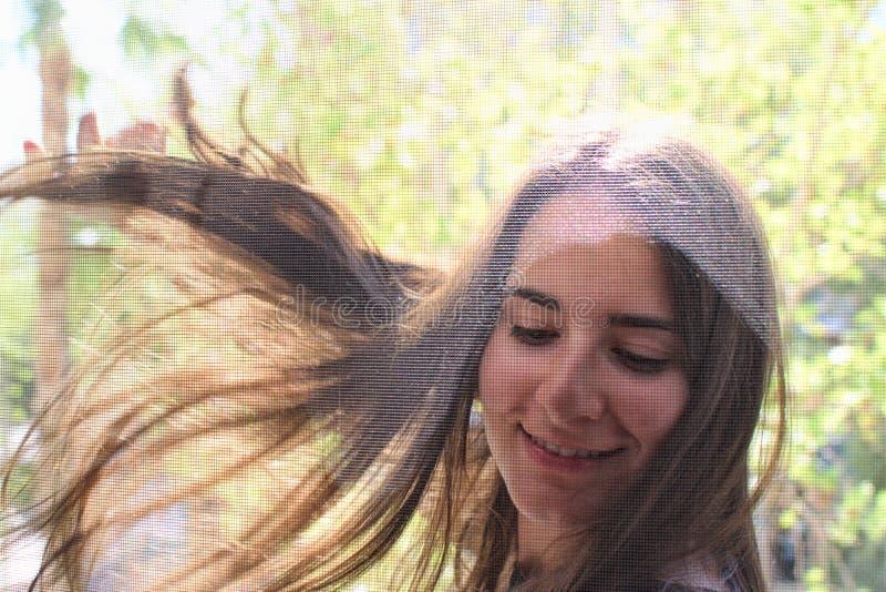 微笑和挥动与照相机的一个俏丽的女孩的画象 免版税库存照片