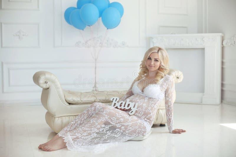 微笑和接触她的腹部的美丽的白肤金发的孕妇我 库存图片