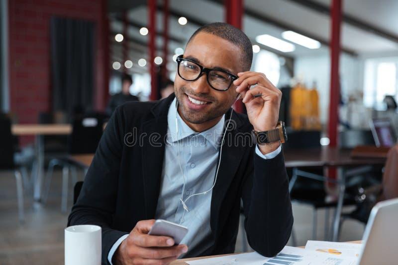 微笑和接触他的玻璃的商人 免版税库存图片