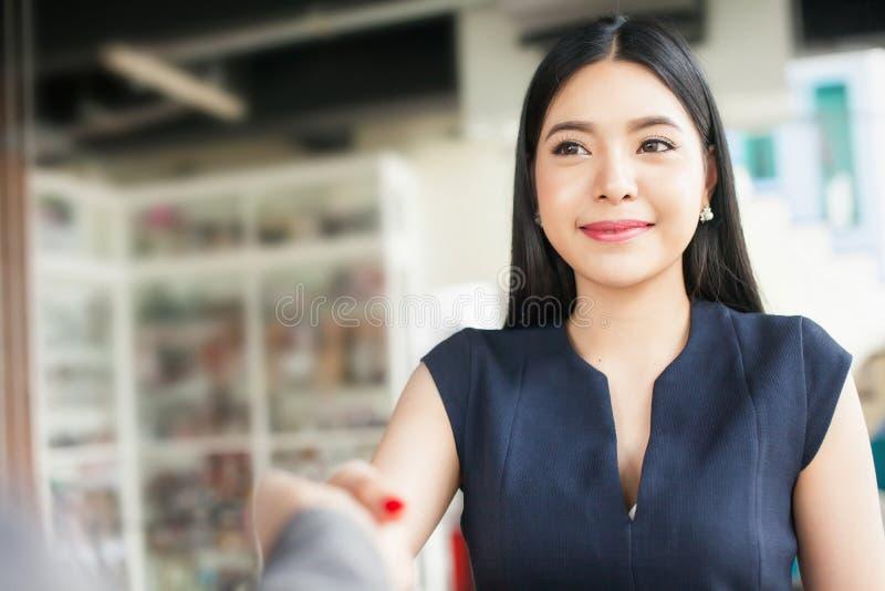 微笑和握手的确信的亚裔女实业家 免版税库存图片