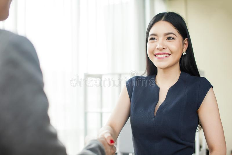 微笑和握手的美丽的亚裔女实业家 免版税库存图片