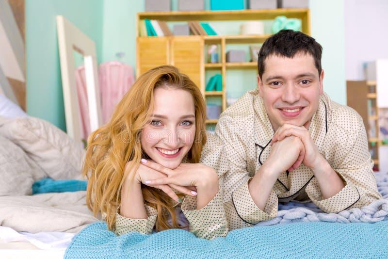 微笑和摆在床上的年轻夫妇 免版税库存照片