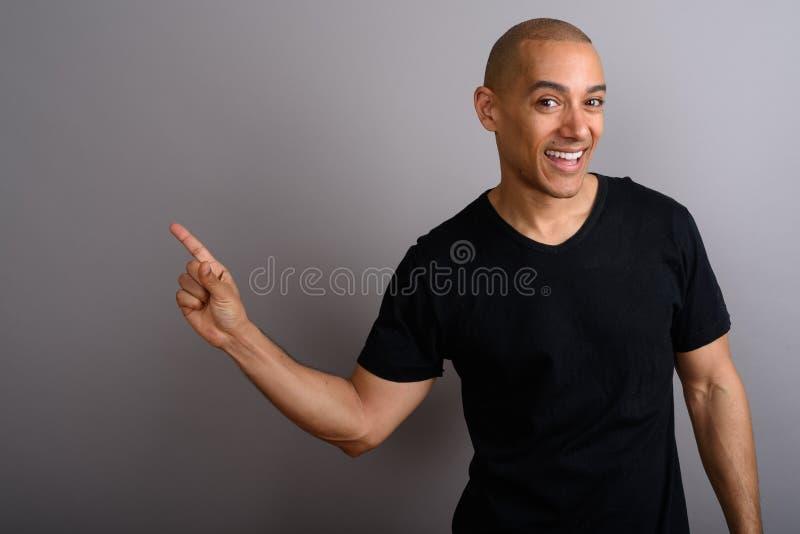 微笑和显示与指向的英俊的秃头人手指的拷贝空间 库存照片