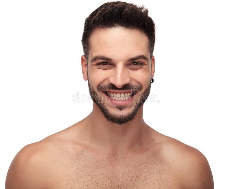 微笑和显示他的牙的不穿衣服的未剃须的人 免版税库存照片