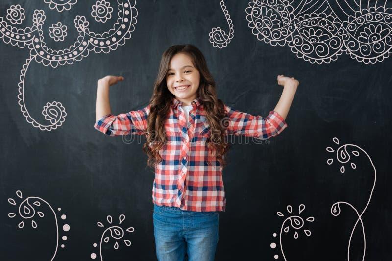 微笑和显示在墙壁上的正面女孩一件可爱的装饰品 库存照片