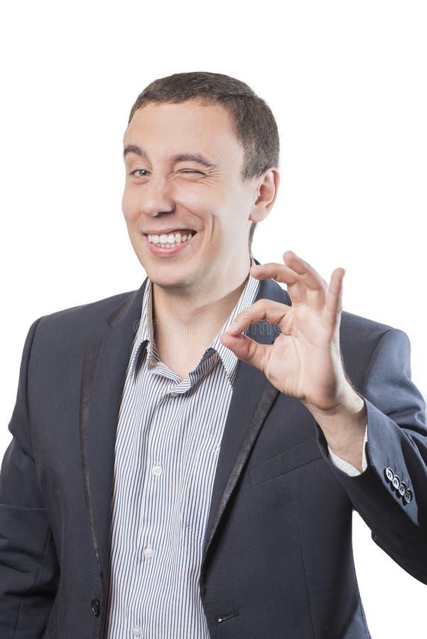 微笑和显示姿态Ok的商人,隔绝在白色背景 免版税库存图片