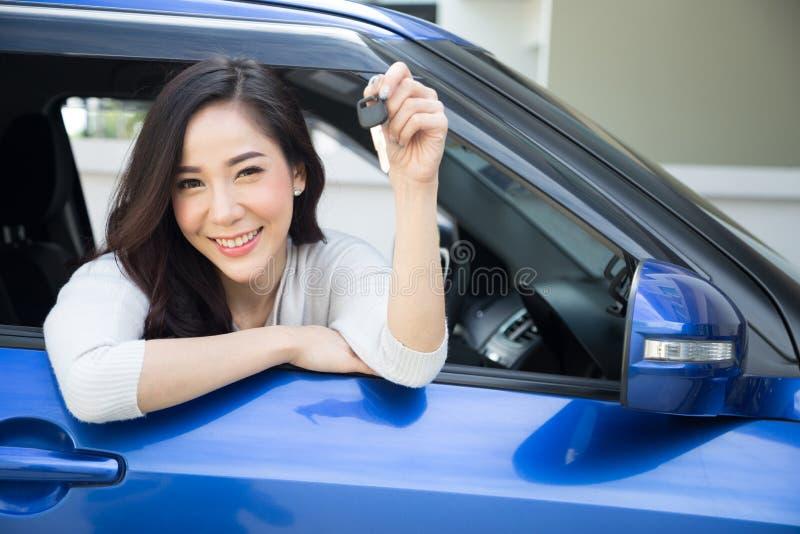 微笑和显示新的汽车钥匙的年轻愉快的亚裔汽车司机妇女 库存照片