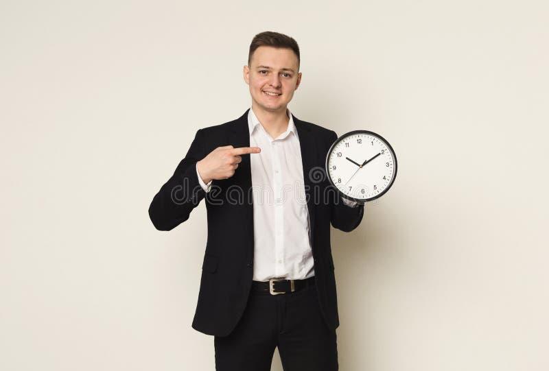 微笑和显示时钟的愉快的商人 图库摄影