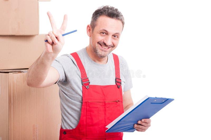 微笑和显示胜利的搬家工人人拿着剪贴板 库存图片