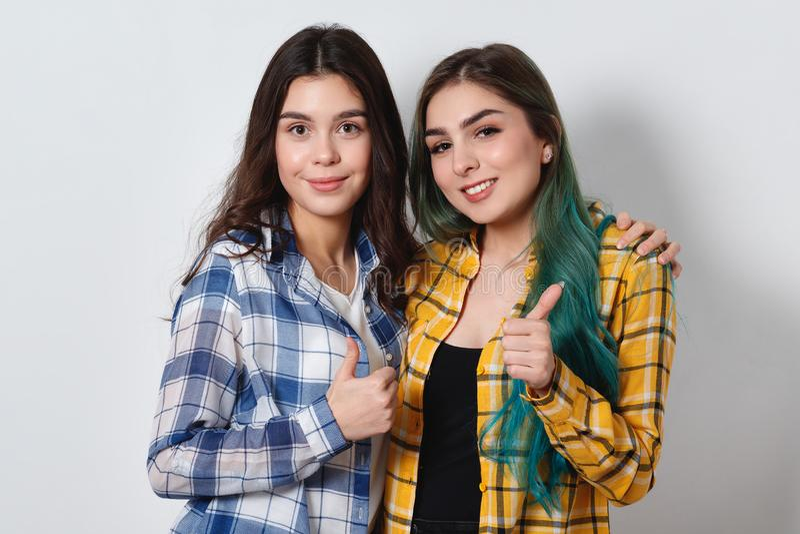 微笑和显示赞许的两美女 在空白背景 免版税库存图片