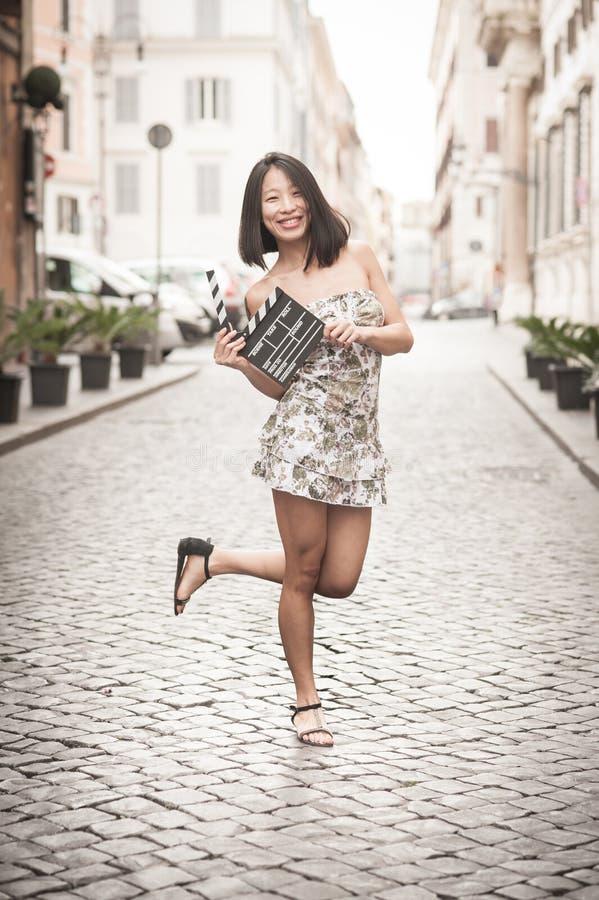 微笑和显示clapperboard都市场面的年轻亚裔妇女 库存照片