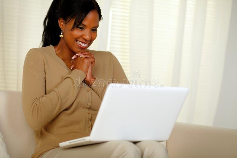 微笑和查找对膝上型计算机的愉快的少妇 免版税库存照片
