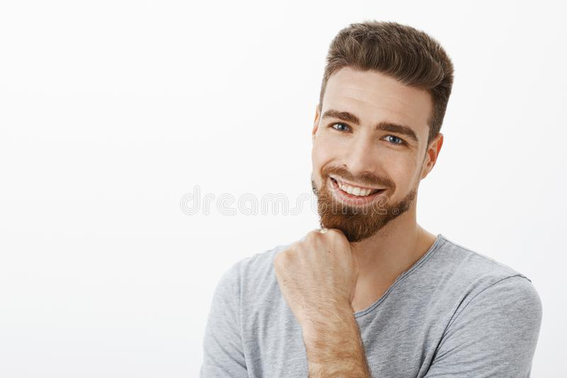 微笑和注视欢欣与逗人喜爱的蓝色的照相机的成功和愉快的自信的男性企业家摩擦胡子 图库摄影