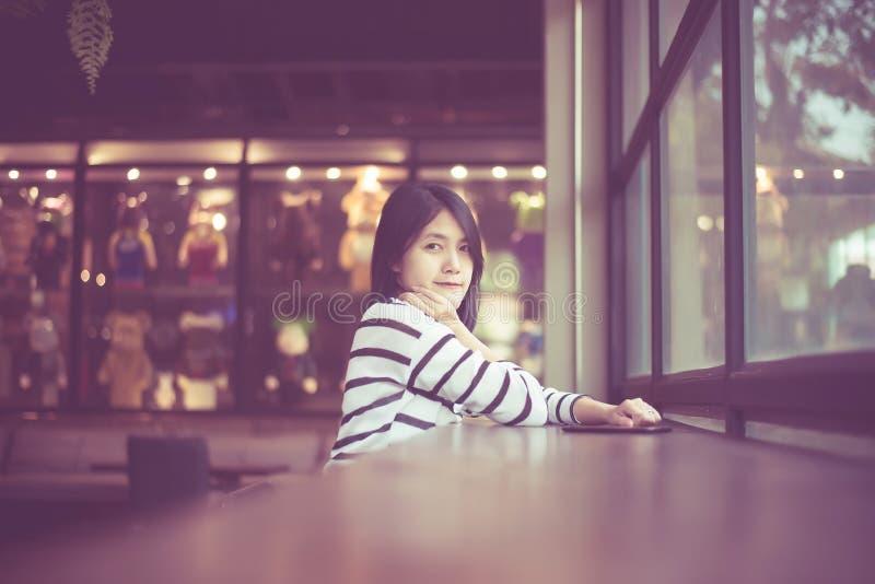 微笑和看在咖啡馆咖啡馆的美丽的亚裔妇女画象照相机,满意和新鲜对正面认为,葡萄酒co 免版税库存照片