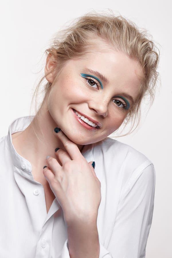 微笑和看在照相机的一名年轻白肤金发的妇女的情感画象 免版税图库摄影