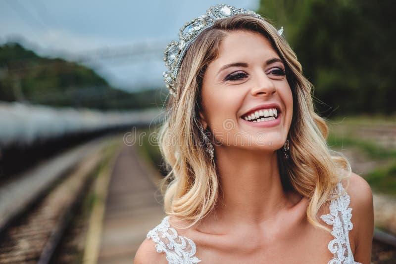 微笑和看对边的白肤金发的新娘 免版税库存照片