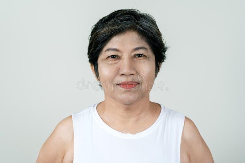 微笑和看照相机的可爱的资深亚裔老妇人画象在充满白色背景感觉的演播室假定 免版税库存图片