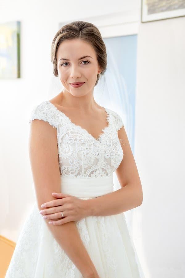 微笑和看照相机的新娘户内 库存照片