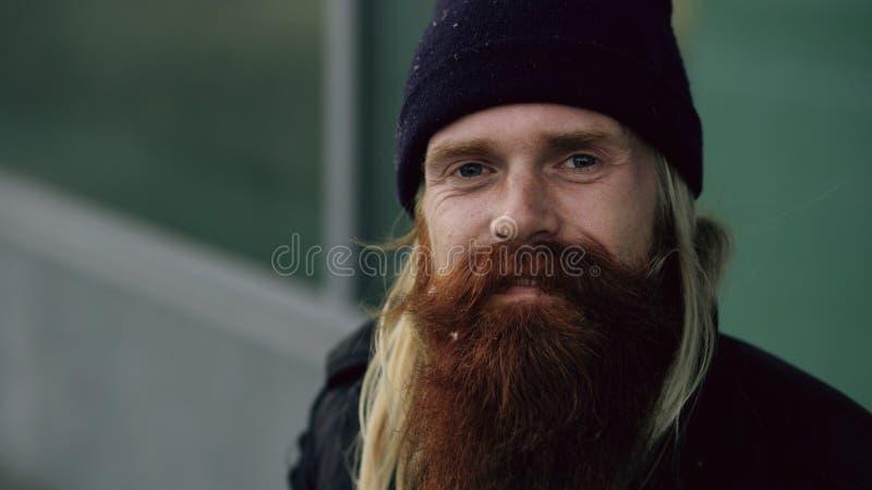 微笑和看照相机的醉酒的无家可归的困人,当坐长凳边路时 库存照片