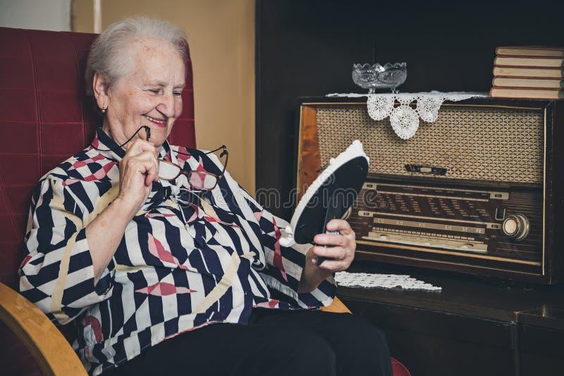 微笑和看老照片框架的资深妇女 免版税库存照片