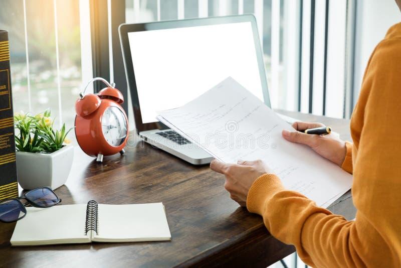 微笑和看膝上型计算机屏幕的可爱的年轻美丽的企业家妇女,运转从家 免版税库存图片