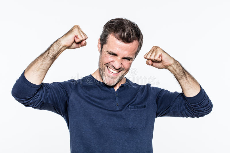 微笑和笑与拳头的快乐的年轻有胡子的人 免版税图库摄影