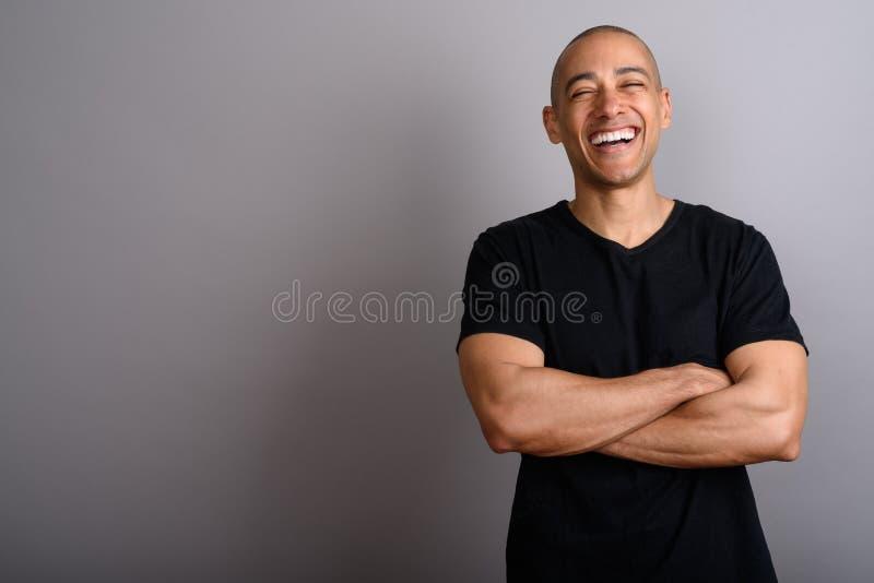 微笑和笑与胳膊的愉快的秃头人横渡 免版税图库摄影