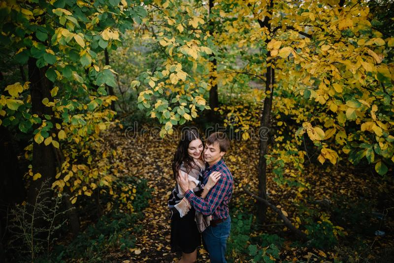 微笑和笑在秋天森林里的愉快的年轻夫妇 库存照片