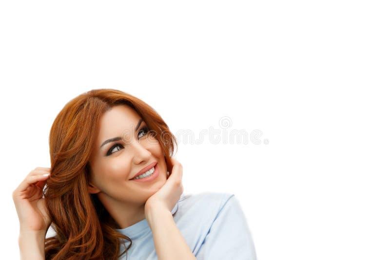 微笑和考虑某事的年轻美女 免版税图库摄影