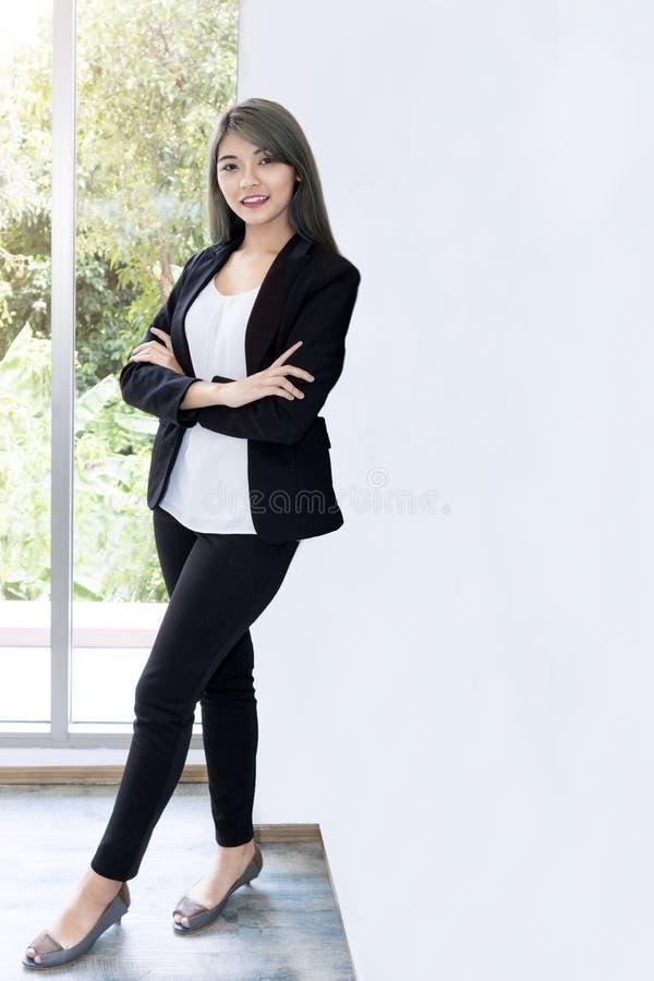 微笑和考虑项目工程的年轻女实业家在办公室 库存图片