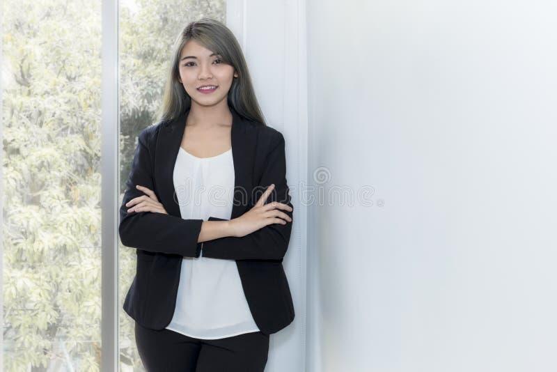 微笑和考虑项目工程的年轻女实业家在o 库存照片