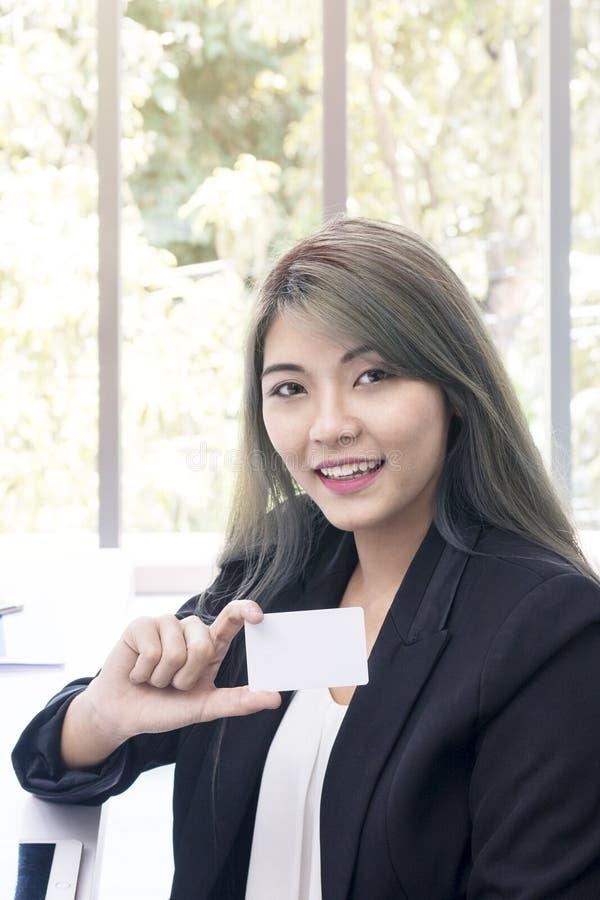 微笑和考虑项目工程的年轻女实业家在o 免版税库存照片