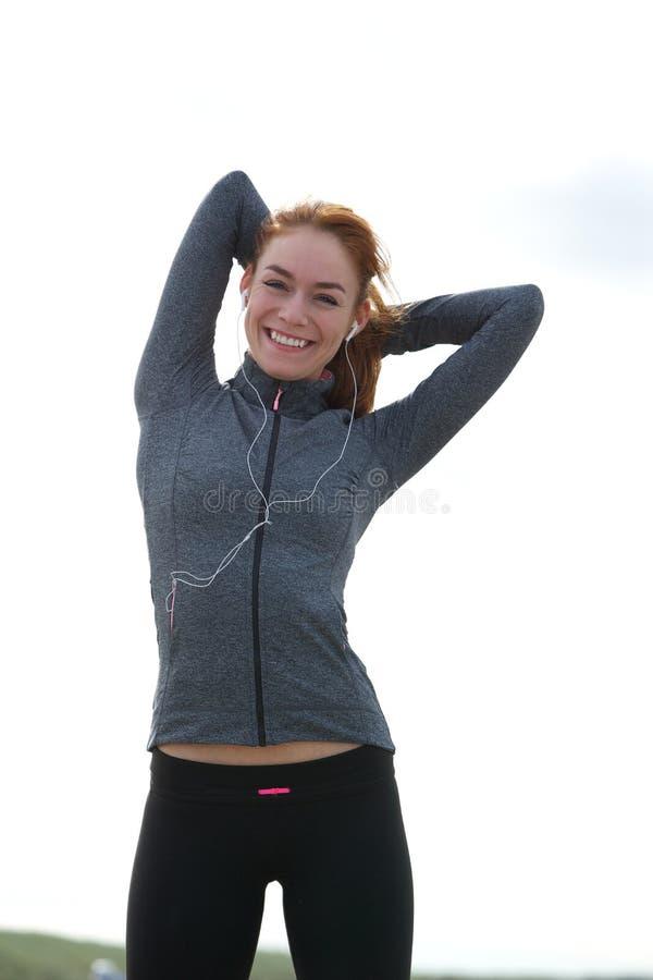 微笑和舒展肌肉的少妇在锻炼前 免版税图库摄影
