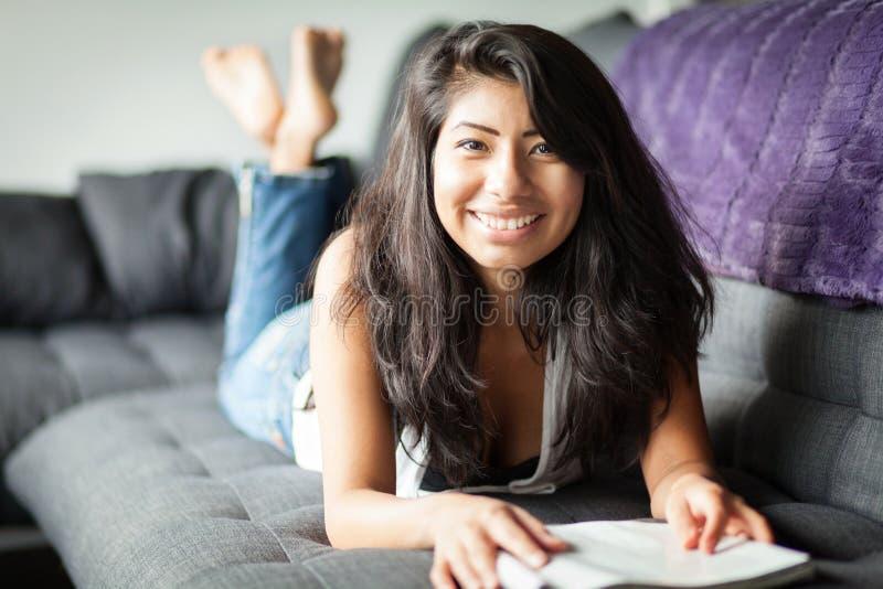 微笑和读杂志的年轻西班牙妇女 沙发的家 免版税库存图片
