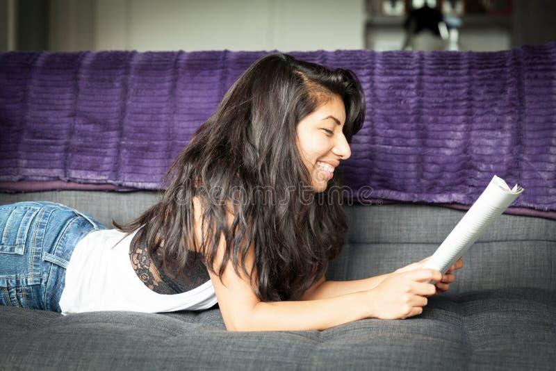 微笑和读杂志的年轻西班牙妇女 沙发的家 Profil 图库摄影