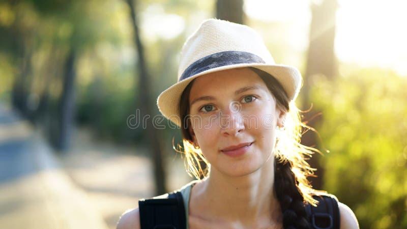 微笑和调查照相机的可爱的旅游女孩特写镜头画象,当远足美丽的森林时 库存照片