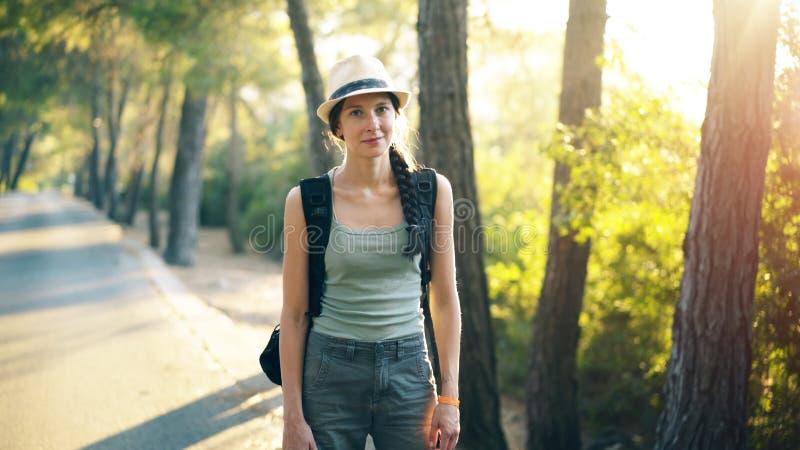 微笑和调查照相机的可爱的旅游女孩画象,当走和远足美丽的森林时 库存照片