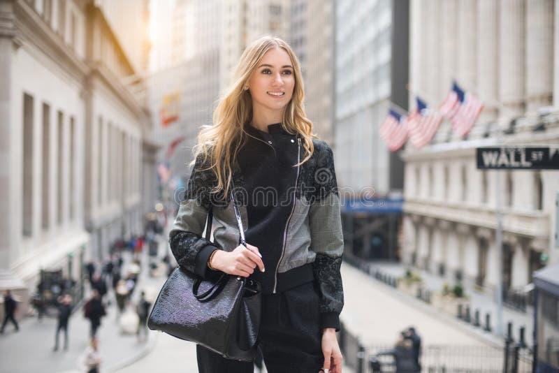 微笑和走到与一个袋子的法院的美丽的典雅的律师女商人在城市街道上 库存图片