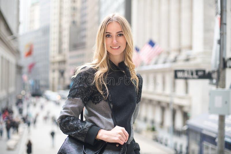 微笑和走到与一个袋子的法院的美丽的典雅的律师女商人在城市街道上 图库摄影