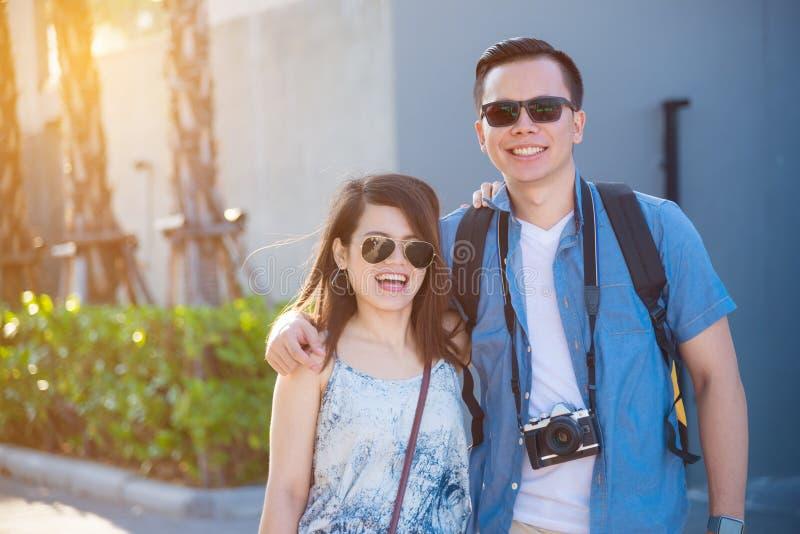 微笑和走在街道上的年轻夫妇 库存图片