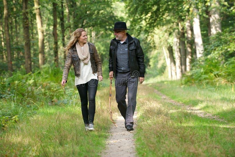 微笑和走本质上的父亲和女儿 免版税库存照片