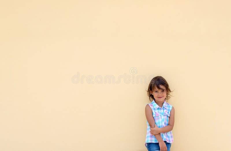 微笑和possing在黄色墙壁旁边的女孩 库存图片
