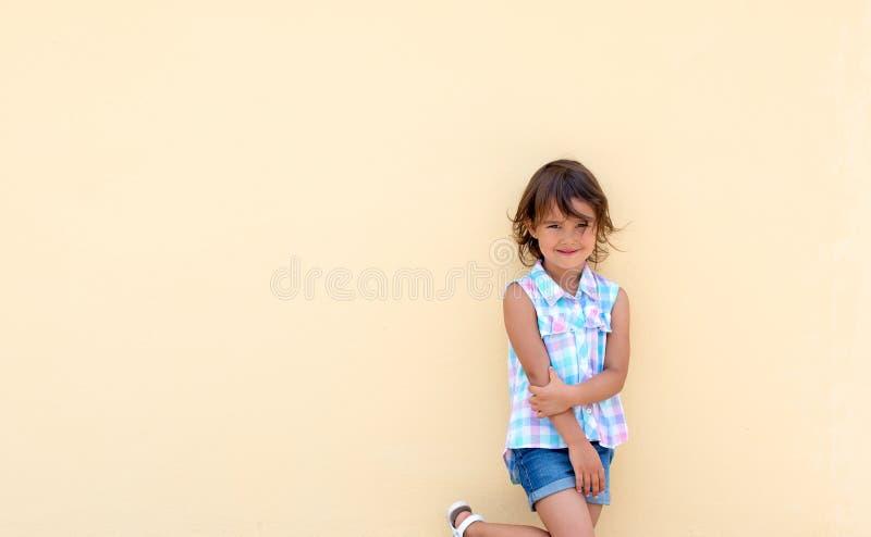 微笑和possing在黄色墙壁旁边的女孩 库存照片