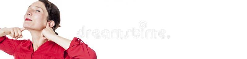微笑嘲笑的妇女塞住她的手指在耳朵,白色全景 库存照片